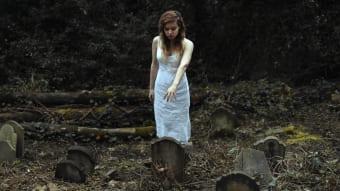 Женщина у могилы на погосте
