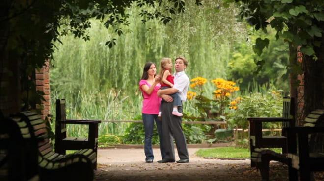 Счастливая семейная пара в саду с хвоей